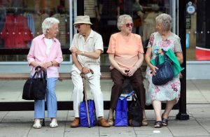 Elderly people sit with their shopping bags as they wait for transportation at a bus stop in Hastings, U.K., on Tuesday, July 23, 2013. U.K. retail sales rose for a second month in June as discounts at department stores drove demand for clothes and electrical products. Photographer: Chris Ratcliffe/Bloomberg via Getty Images