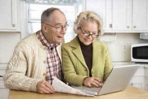 Senior couple working on laptop computer